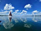Fotografie Segelboot auf einem schönen See bei blauem Himmel und angenehmer grüner Landschaft Hintergrund und schöne Reflexion auf der Wasseroberfläche. Segeln ist eine beliebte Sportart und Aktivität. Verschwommene Sicht