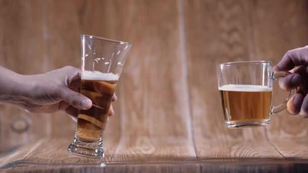 Sklenice a hrnek chutného piva stojí na hnědém pozadí. Vonné pivo osvětlené krásným světlem stimuluje chuť k jídlu.