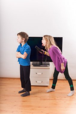 Siblings conflict over the remote control in front of the TV