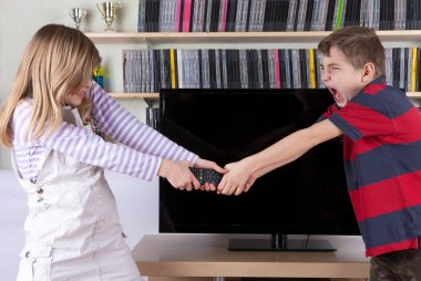 Siblings fighting over the remote control in front of the TV