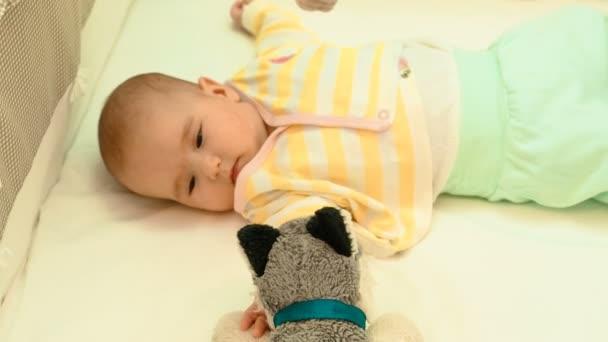 Roztomilé novorozeně hraní s plyšovou hračkou v kolíbce