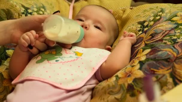 Small beautiful baby drinking milk from a bottle