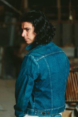 handsome man with long hair brunette in a denim jacket