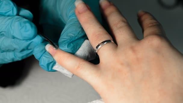 nehtové studio. Manikérka odstranit starý lak na nehty s klientem