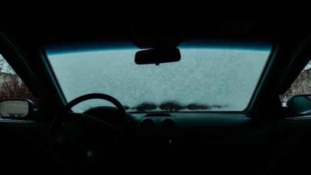 Auto sklo rozmrazené časová prodleva. Sníh rozmrazování na předním skle automobilu