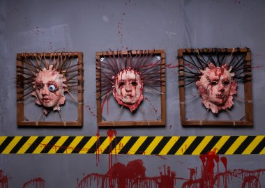 Skins from human heads stuck in square frames in a Halloween hor