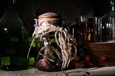 Horrible dead creature with bulging eyes inside jar between glas