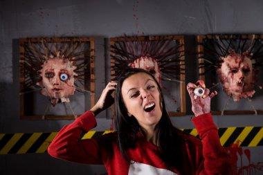 Strange woman holding eyeball in wrinkled hand