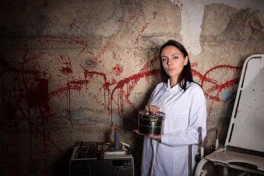 Scientist woman holding an aluminum box in front of a blood spla