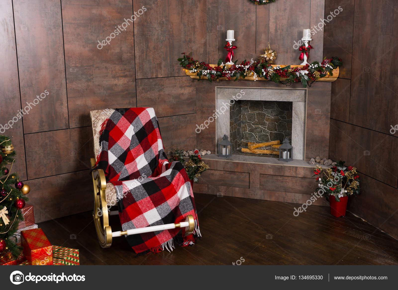 Schaukelstuhl mit einer Decke im Wohnzimmer mit dekorierten m ...