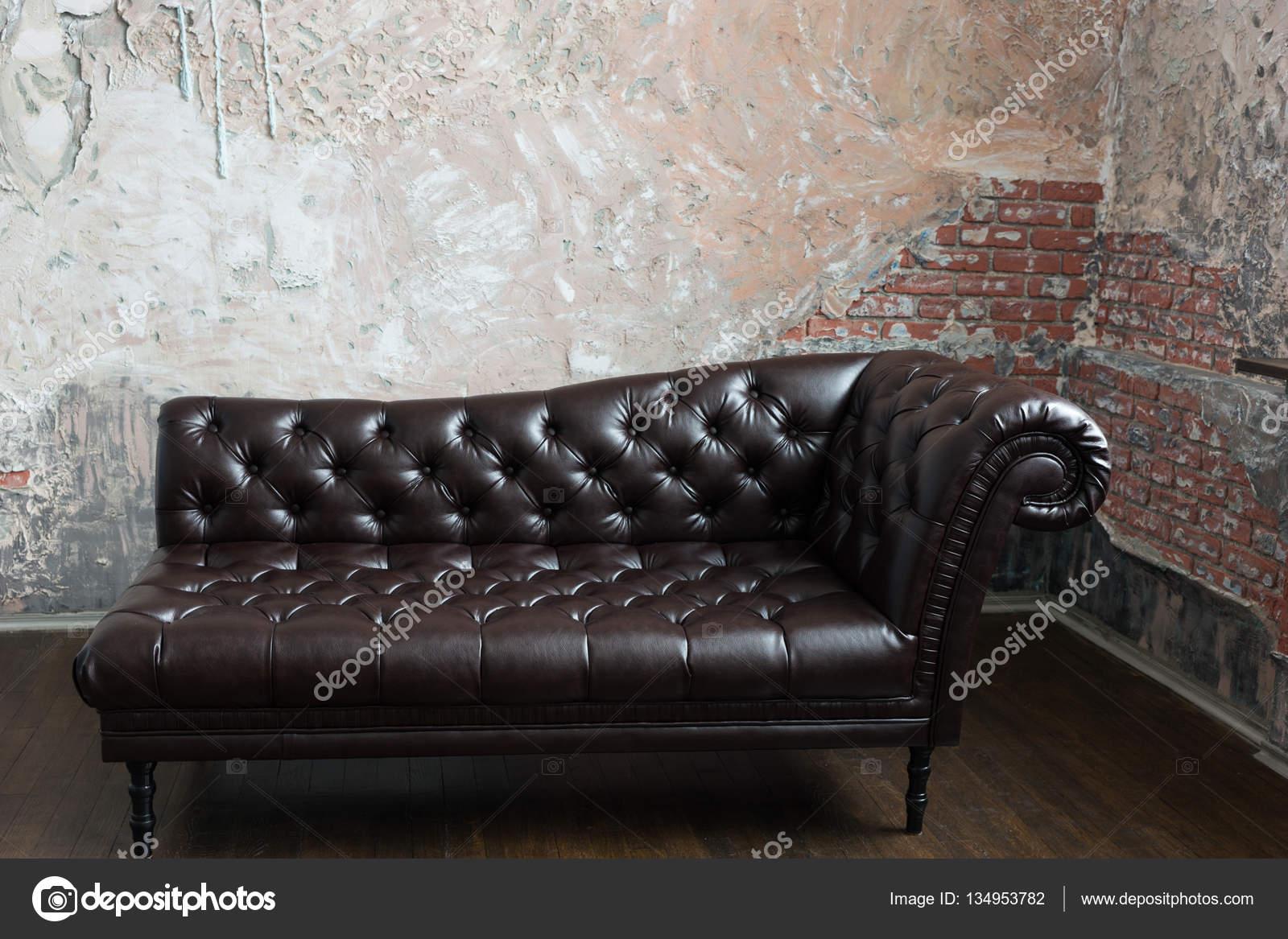 Leerbank in de engelse stijl in de kamer met oude bakstenen wal