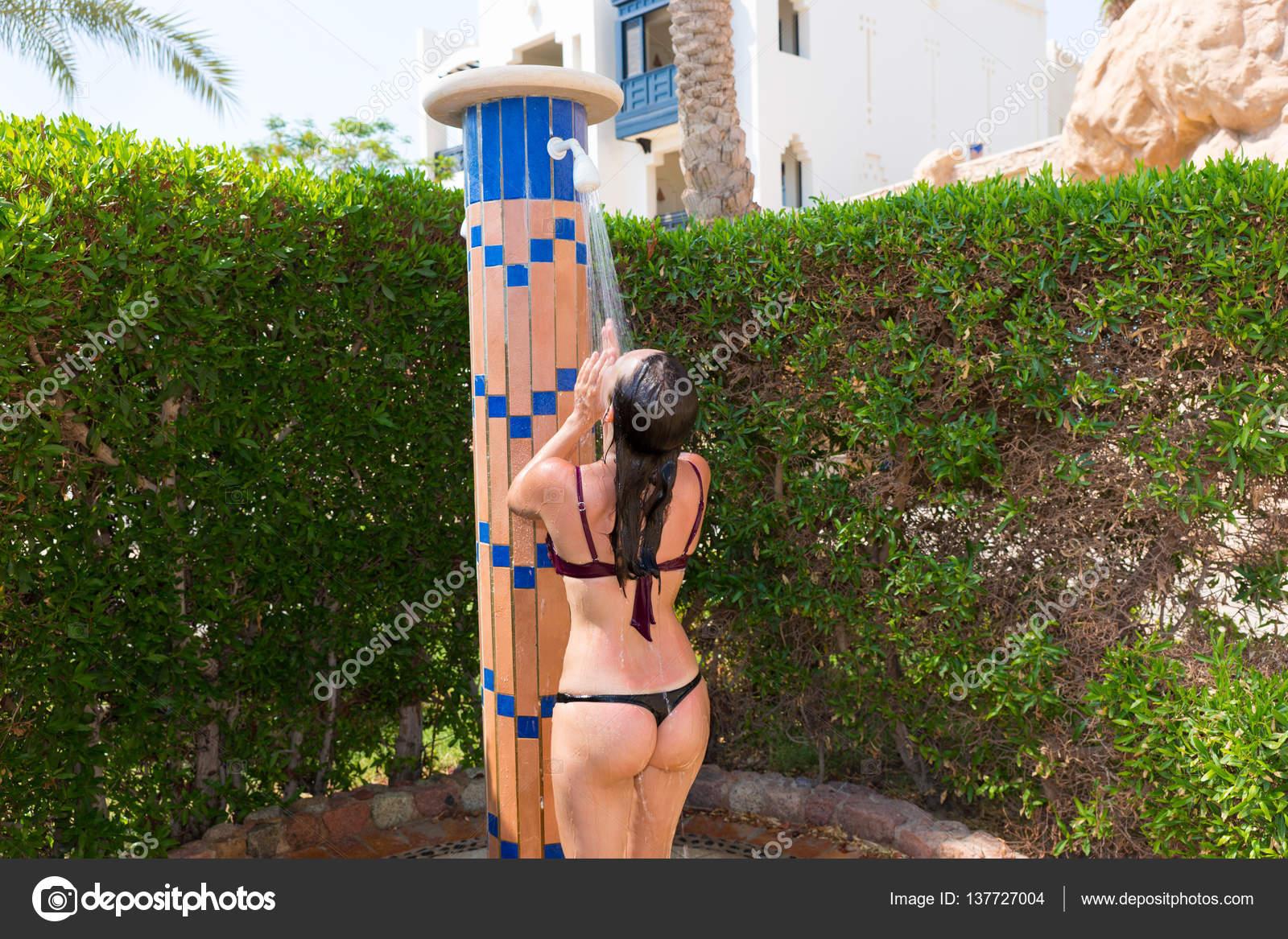 Ragazza che porta i piedi di bikini sotto la doccia all for Piani di casa sotto 500 piedi quadrati