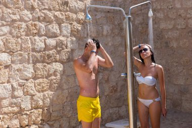 Young couple taking outdoor shower, after swimming