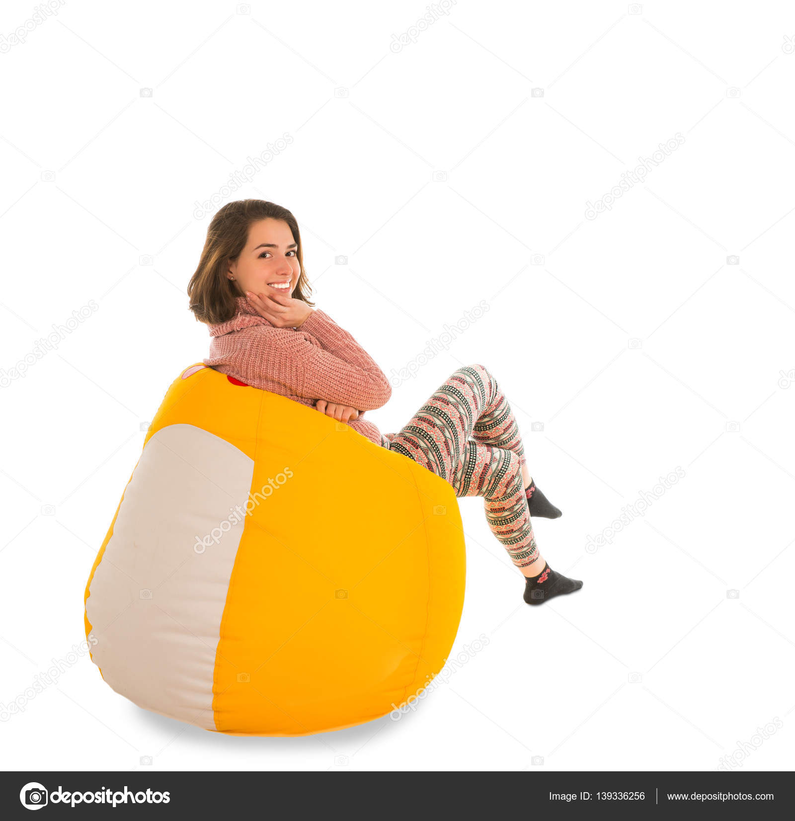 Side view of smiling woman sitting on yellow beanbag chair isola