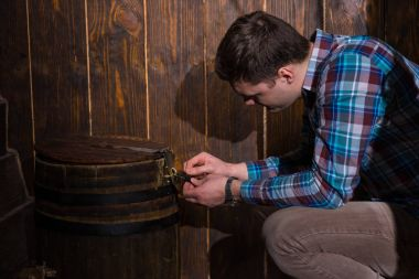 Young man sits near a barrel and trying to solve a conundrum to