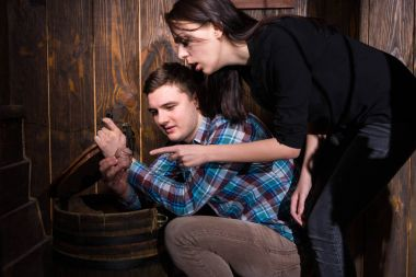 Young man and woman opened a barrel and trying to solve a conund