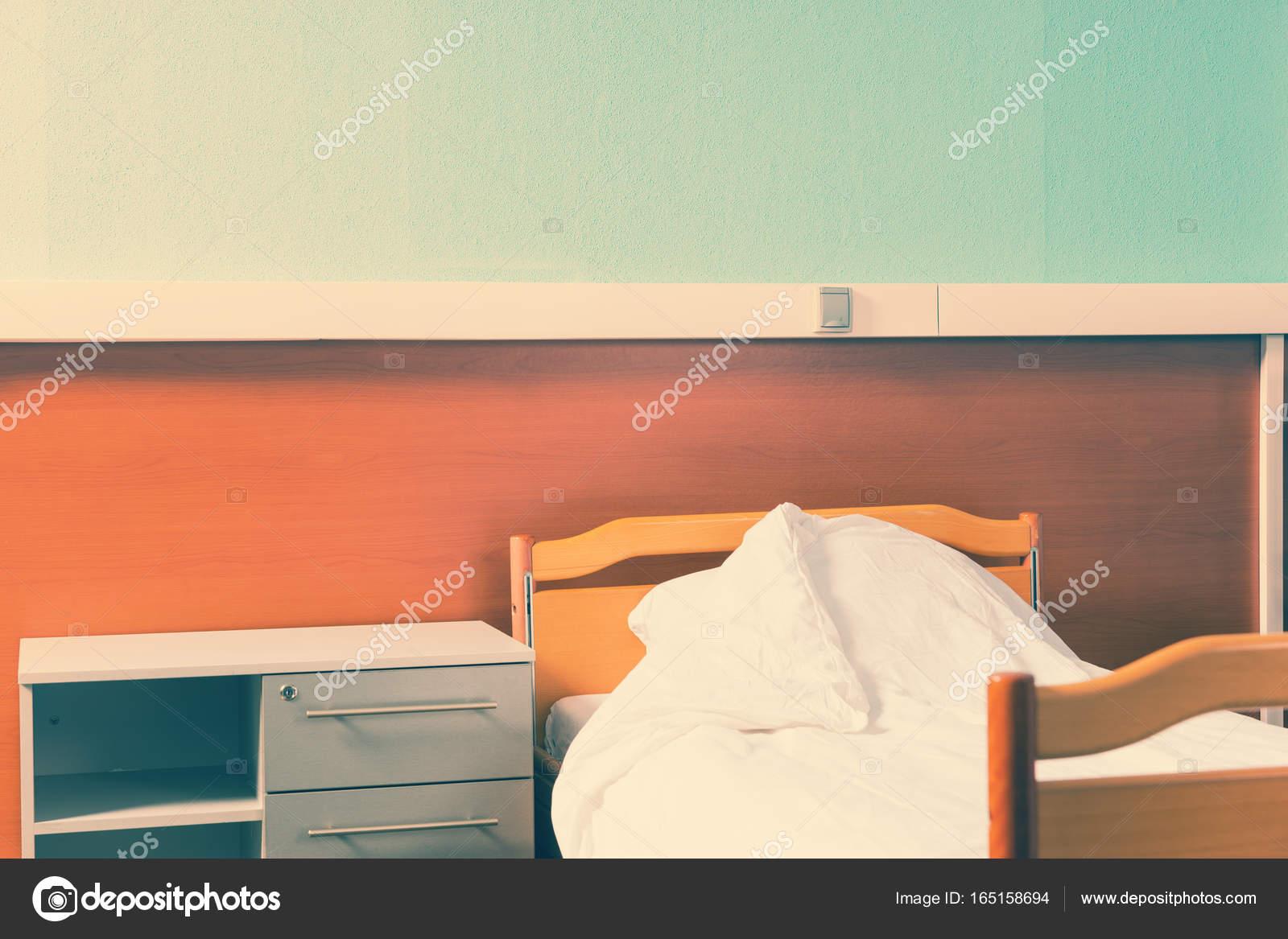 ein nachttisch steht neben dem leeren krankenhaus-bett — stockfoto