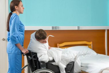 Attractive nurse in uniform pulling wheelchair with ill patient