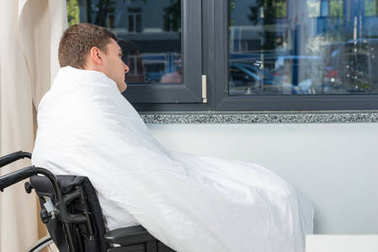 Male ill patient sitting by the window on wheelchair covered wit