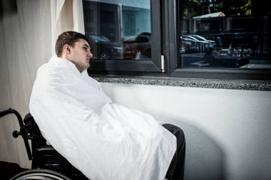 Sad male ill patient sitting by the window on wheelchair covered