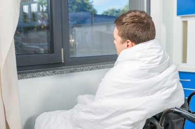 Sad ill patient sitting by the window on wheelchair covered with
