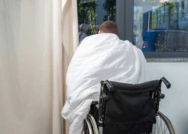 Ill patient sitting by the window on wheelchair covered with qui