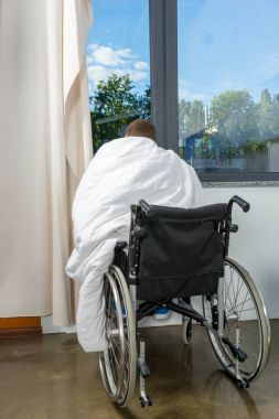 Male young patient sitting by the window on wheelchair covered w
