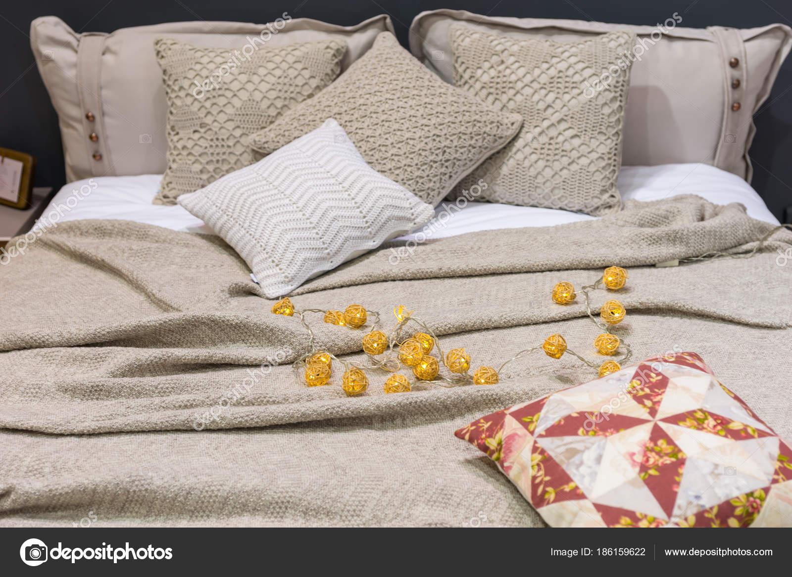Biancheria da letto accogliente con cuscini decorativi in camera da ...