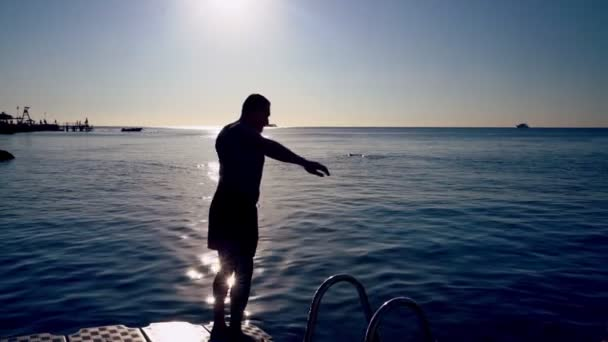 Muž se rýsoval proti slunci na moři