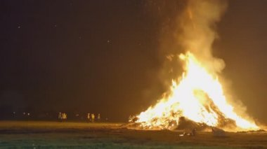 Big bonfire burning in the field at night, people wearing safety vests and helmets standing next to it
