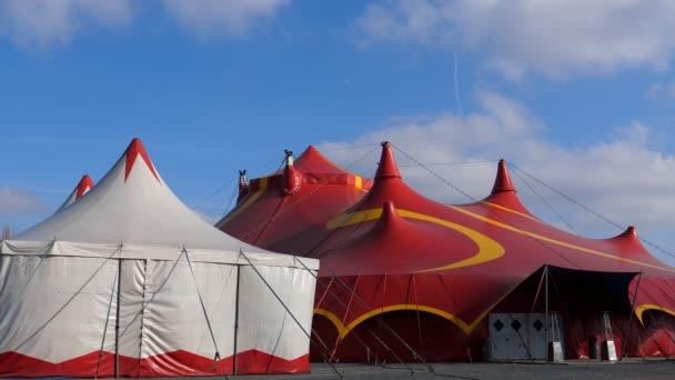 Zwei Zirkuszelte. weiß klein und groß rot mit geschlossener Eingangstür an einem sonnigen, windigen Tag
