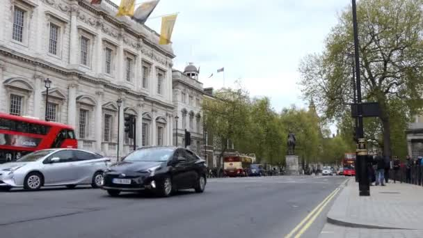 LONDON, ENGLAND, UNITED KINGDOM - APRIL, 2017: Street scene in the heart of United Kingdoms City of Westminster, Central London, showing the Banqueting House, famous red double-decker buses and taxis on Whitehall