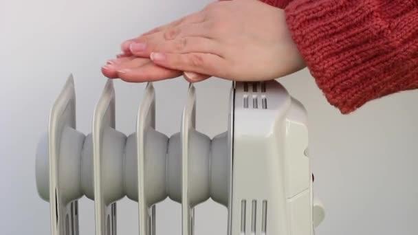 weibliche Hände auf elektrischem Ölkühler in Nahaufnahme auf weißem Hintergrund