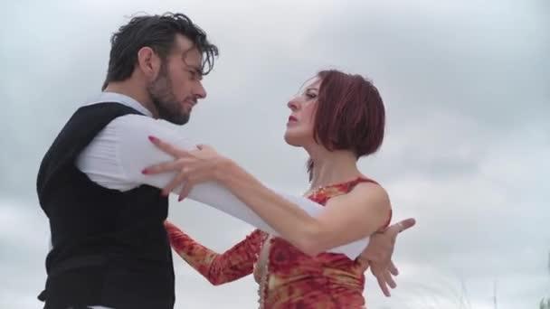 Egy pár tangó táncos szenvedélyesen táncol a felhős égbolton.