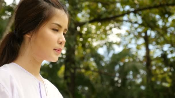 Woman in white clothes smiling during meditation on green trees background