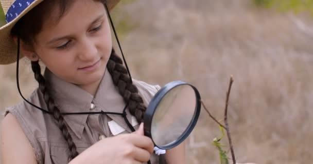 Gyerekek felfedezik a világot. Egy hétéves szalmakalapos kislány, aki tudósosat játszik, nagy zöld rovarokat néz, imádkozó sáskákat egy nagyítóban. Vicces és érdekes gyerekkori történet 4k