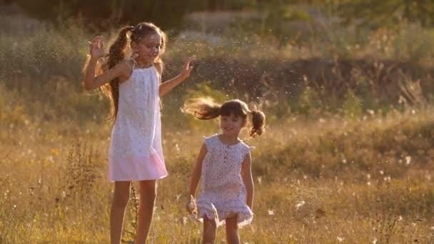Zwei kleine hübsche Schwestern, vier und sieben Jahre alt, spielen mit Wasserspritzern und springen in warmen, hellen Sonnenuntergangsstrahlen auf einer Wiese in der Nähe eines Waldes. Zeitlupe 200 fps