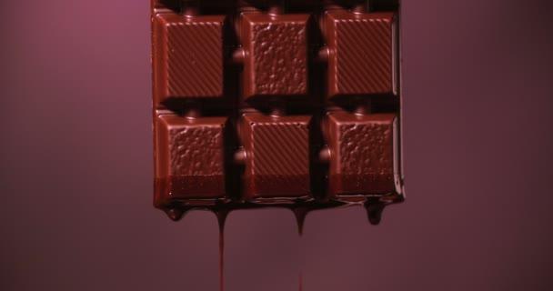 Eine Tafel dunkle Schokolade schmilzt. Geschmolzene Schokolade fließt von ihr auf einem violetten Studiohintergrund herab. 4K Zeitlupe 50 fps