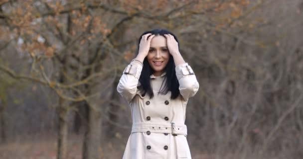 Portrét atraktivní brunetky po třicítce pózující a usmívající se na kameru v krásném podzimním lese. Bruneta v bílém zákopu s tmavými dlouhými vlasy a hnědýma očima. 50 snímků za sekundu zpomalení 4k