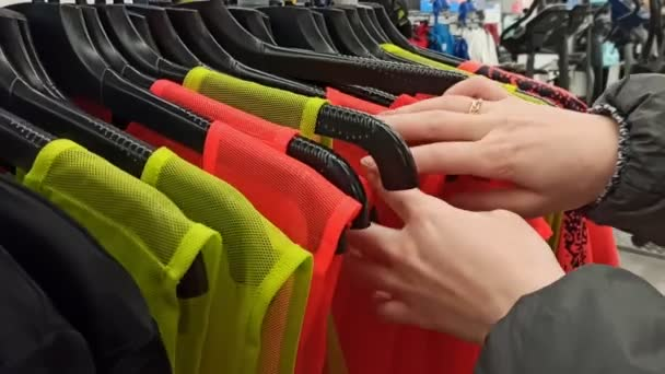 looking for t-shirts on a hanger in a store