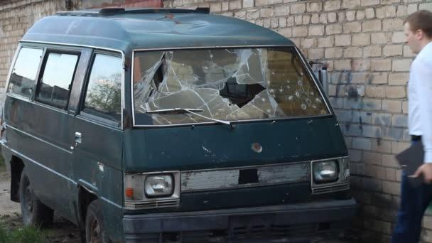 muž kontroluje minibus rozbité auto, pojištění