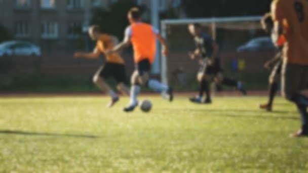 Hráč a jeho tým útočí, amatérský fotbal na malém stadionu v pomalém pohybu