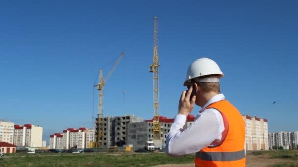 Náčelník mluví po telefonu na pozadí výstavby bytového domu