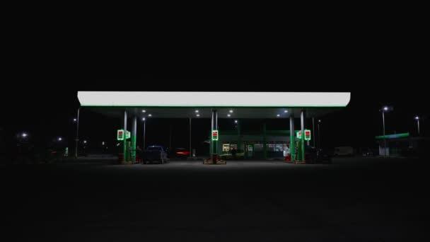 Načasovaná čerpací stanice v noci. Auta jsou natankovaná benzínem na benzínce. Obchodní ropný koncept