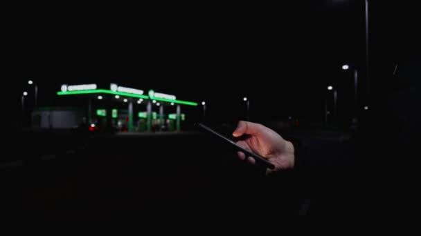 Muž používá mobilní aplikaci na smatrphonu v blízkosti čerpací stanice v noci. Auta jsou poháněna benzínem na čerpací stanici.