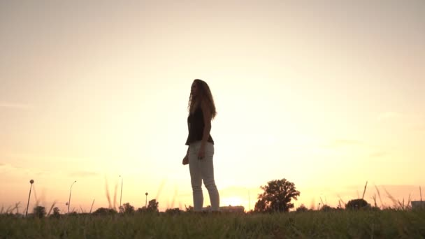 schöne Mädchen springen auf einem Hintergrund von sonnigen Sonnenuntergang am Abend, Zeitlupe, psychologische Erleichterung