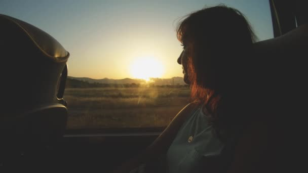 Turista lány néz át a busz ablakán a természet táj naplementekor mozog. Városnézés és utazás. Nyaralás Montenegróban, kirándulás