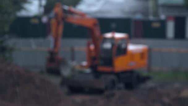 Radladerbagger mit Schaufel und Regen im Vordergrund. verschwommen. Das Mehrzweckfahrzeug ist auf der Baustelle unterwegs, um Lade- und Aufladearbeiten durchzuführen. Traktor mit Schaufel