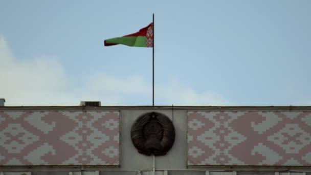 Weißrussisches Wappen und Ornament. Weißrussische Flagge weht im Wind vor blauem Himmel, Kopierraum, nationale