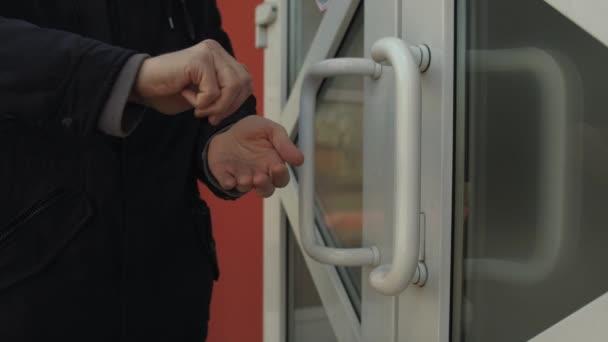 Egy férfi fertőtleníti a kezét egy fertőtlenítővel a bolt bejáratánál. Egy férfi megérinti a bejárati ajtó kilincsét és fertőtleníti a kezét. A fertőzés és a coronovírus elleni védelem fogalma